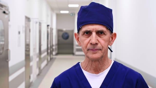 vidéos et rushes de portrait de médecin mûr dans le couloir - infirmier