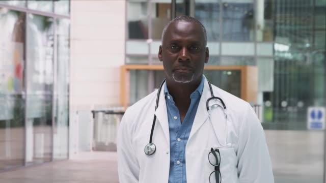 modern hastane binasında ayakta beyaz ceket ve stetoskop giyen olgun doktor portresi - yavaş çekimde vuruldu - orta plan plan türleri stok videoları ve detay görüntü çekimi