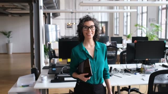 porträt der reifen exekutive mit laptop im büro - weibliche führungskraft stock-videos und b-roll-filmmaterial