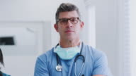 istock Portrait Of Mature Male Doctor Wearing Scrubs Standing In Busy Hospital Corridor 1205546644