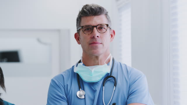 Portrait Of Mature Male Doctor Wearing Scrubs Standing In Busy Hospital Corridor video