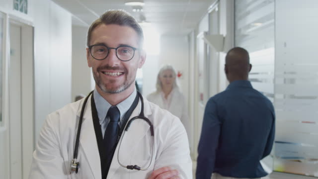 Portrait Of Mature Male Doctor Wearing White Coat With Stethoscope In Busy Hospital Corridor Portrait of smiling mature male doctor wearing white lab coat standing in busy hospital corridor - shot in slow motion dermatology stock videos & royalty-free footage