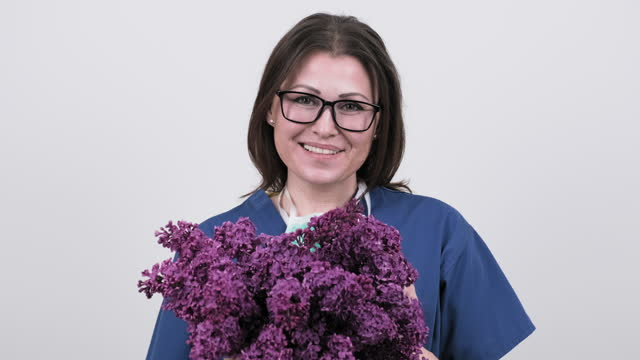 Portrait of mature smiling female doctor in glasses with protective medical mask holding bouquet of flowers. Doctor's Day Portrait of mature smiling female doctor in glasses with protective medical mask holding bouquet of flowers. Doctor's Day, World Health Day, National Nurses Day. High quality 4k footage world health day stock videos & royalty-free footage