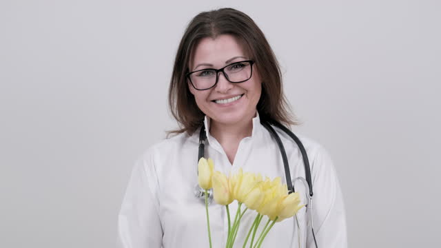 Portrait of mature smiling female doctor in glasses with stethoscope holding bouquet of flowers. Portrait of mature smiling female doctor in glasses with stethoscope holding bouquet of flowers. Doctor's Day, World Health Day, National Nurses Day. High quality 4k footage world health day stock videos & royalty-free footage