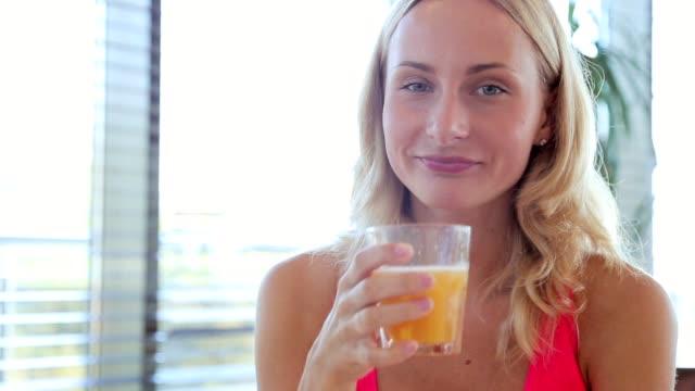 Portrait of mature woman drinking orange juice video