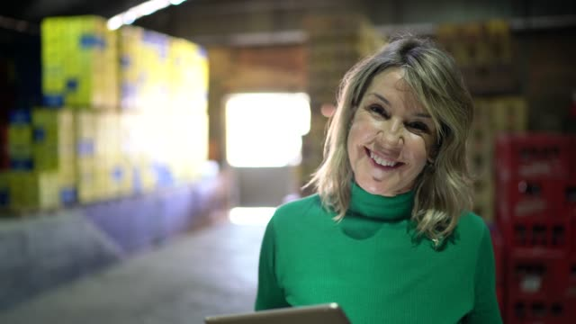 portrait of mature woman using digital tablet at warehouse - direttrice video stock e b–roll