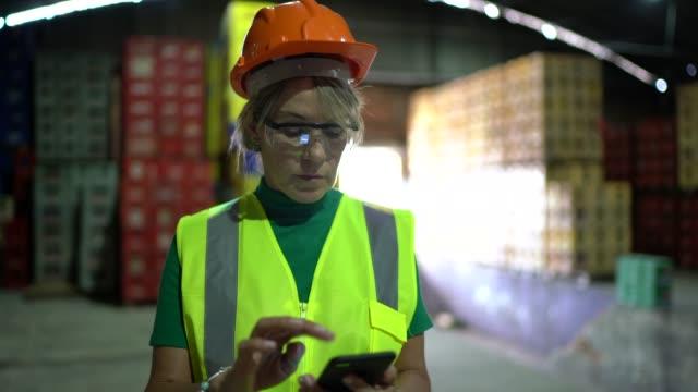 portrait of mature woman using mobile phone at warehouse - prodotti supermercato video stock e b–roll