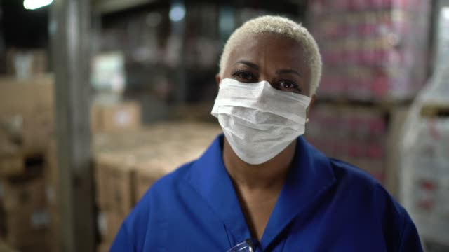 portrait of mature woman wearing face mask working in warehouse / industry - mask стоковые видео и кадры b-roll