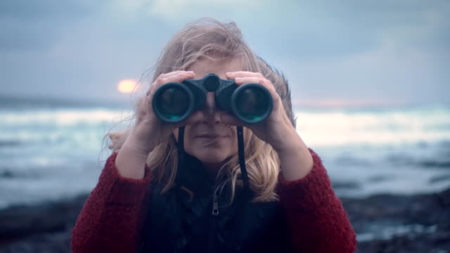 portrait of mature woman with binoculars on a storm background against a dramatic sky background video