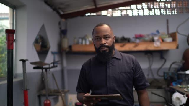 Portrait of mechanic man using digital tablet in auto car repair