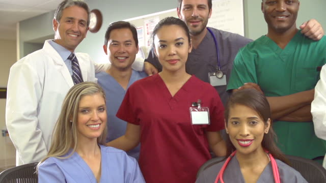 Portrait Of Medical Team At Nurses Station Camera tracks along various members of medical team at nurses station in slow motion.Shot on Sony FS700 in PAL format at a frame rate of 50fps group of objects stock videos & royalty-free footage