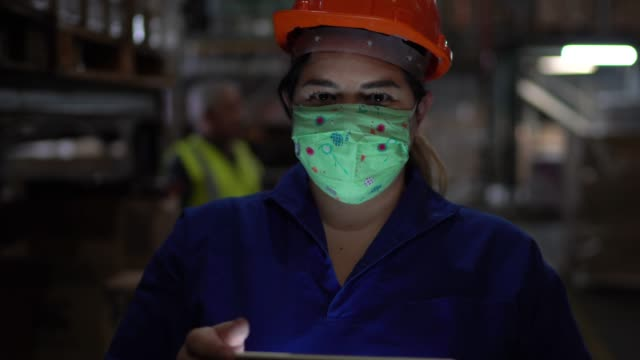 portrait of mid adult woman wearing face mask using digital tablet - working at warehouse / industry - face mask stock videos & royalty-free footage