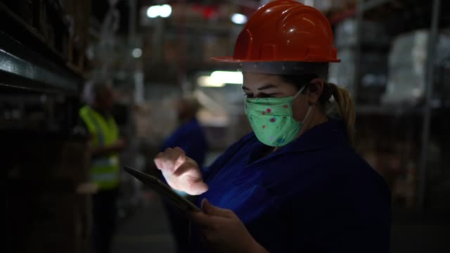 Portrait of mid adult woman wearing face mask using digital tablet - working at warehouse / industry video
