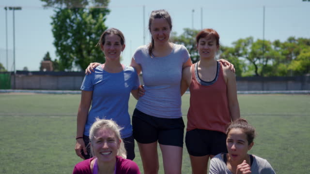 Portrait of mid adult women standing on soccer field before the game Portrait of five mid adult women standing on soccer field before the game, smiling, embracing and looking at camera pre game stock videos & royalty-free footage