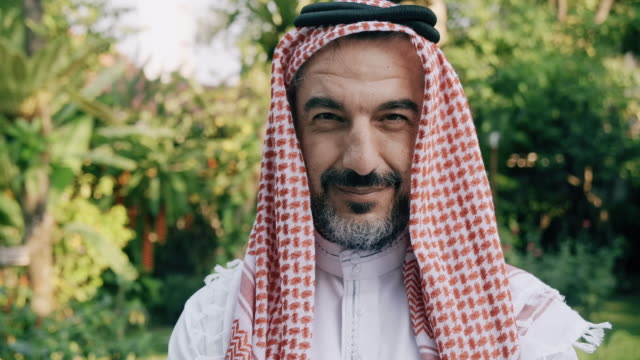 Portrait of middle east man with green tree in background.