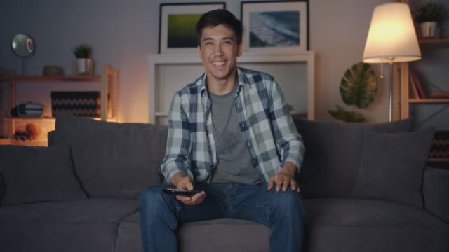 vídeos de stock, filmes e b-roll de retrato do homem novo da raça misturada que presta atenção à tevê na noite que ri tendo o divertimento - solteiros jovens