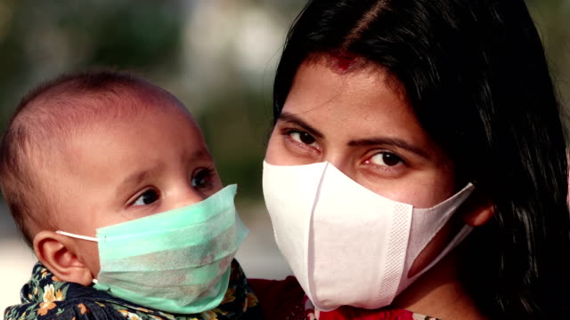 Portrait of Mother and baby daughter covering face with pollution mask against COVID-19 or Coronavirus