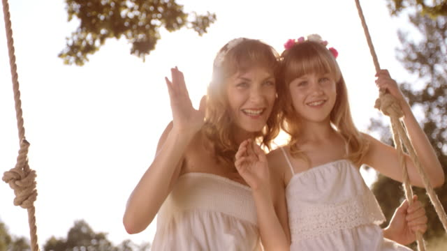 SLO MO Portrait of mother and daughter waving from a swing video