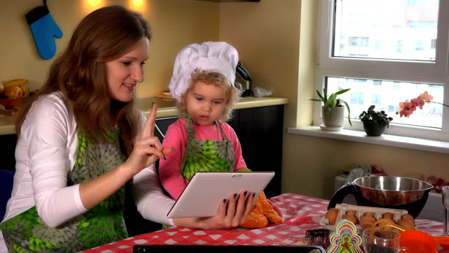Portrait of mother and her cutie daughter using tablet computer in kitchen Portrait of mother and her cutie daughter using tablet computer while looking for recipe on internet. Little girl and her mom baking together in the kitchen at home. Static shot. 4K UHD recipe stock videos & royalty-free footage