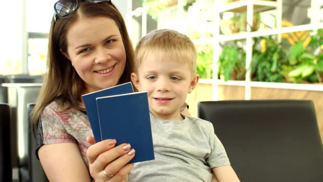 Portrait of mother with child at the airport with passports and tickets in hand