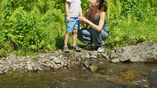 Portrait of Mother with her son are sitting near a stream video
