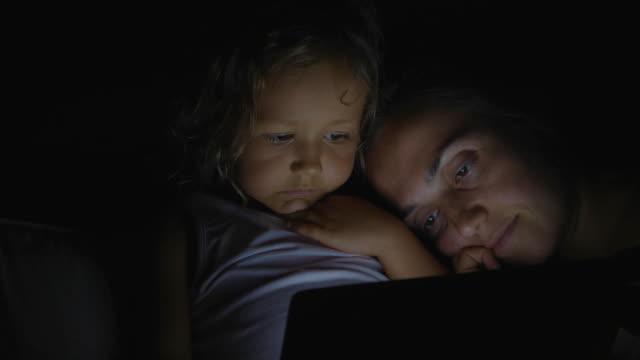 porträt der mutter mit töchterchen mit tablet im bett bei nacht zu hause. - alleinerzieherin stock-videos und b-roll-filmmaterial