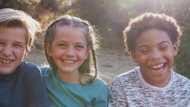 vídeos y material grabado en eventos de stock de retrato de niños multiculturales pasando el rato con amigos en el campo juntos - grupo multiétnico