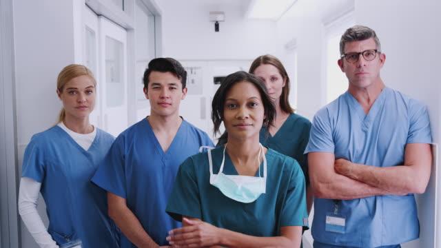 hastane koridorunda duran çok kültürlü sağlık ekibinin portresi - cerrahi önlük stok videoları ve detay görüntü çekimi