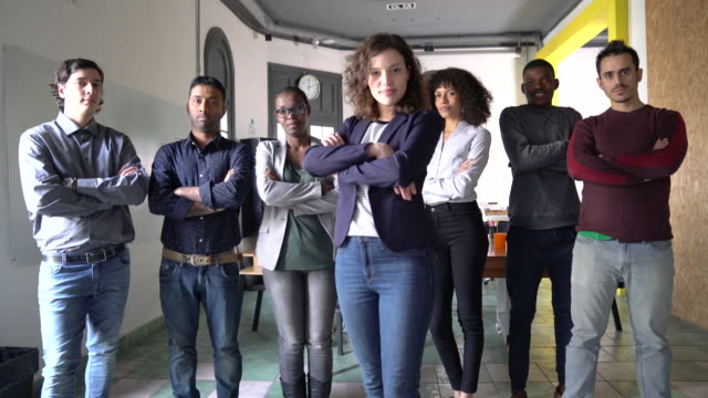 Portrait of multi-ethnic business team at office Portrait of confident male and female executives standing with arms crossed. Multi-ethnic business team is in smart casuals. They are at office. medium group of people stock videos & royalty-free footage