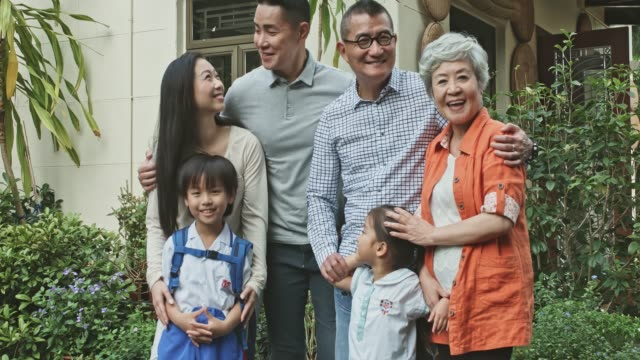 stockvideo's en b-roll-footage met portret van multi-generational chinese familie staande in de achtertuin tuin thuis - chinese etniciteit
