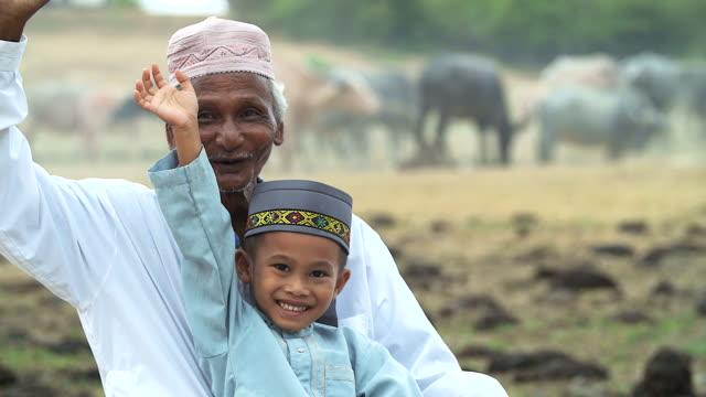 Portrait of muslim grandfather and grandchild with smiley face. video