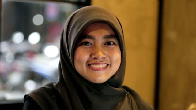 ヒジャーブとイスラム教徒の東南アジア女性のポートレートは笑顔と遊び心のあります。 - インドネシア点の映像素材/bロール