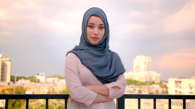 portrait of muslim student in hijab watching into camera standing at the balcony with great city view. - abbigliamento religioso video stock e b–roll