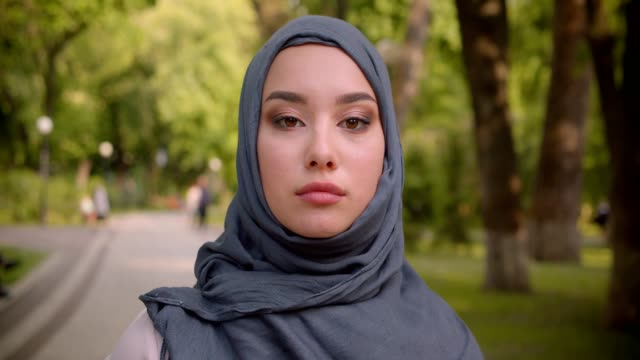 portrait of muslim woman in hijab watching seriously into camera walking in the park. - abbigliamento modesto video stock e b–roll