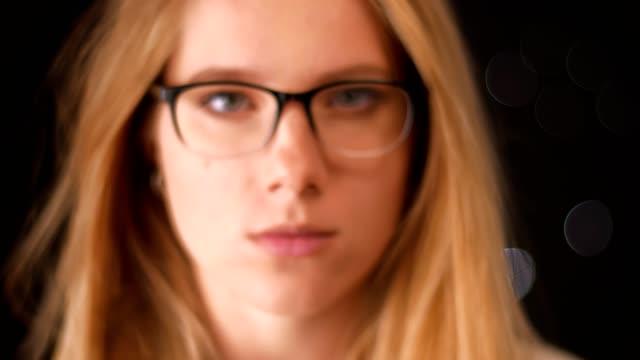 stockvideo's en b-roll-footage met portret van mooie blonde bril kaukasische vrouw op zoek in de camera op de voet, terwijl staande op zwarte achtergrond indoor, wazig illustratie - portait background