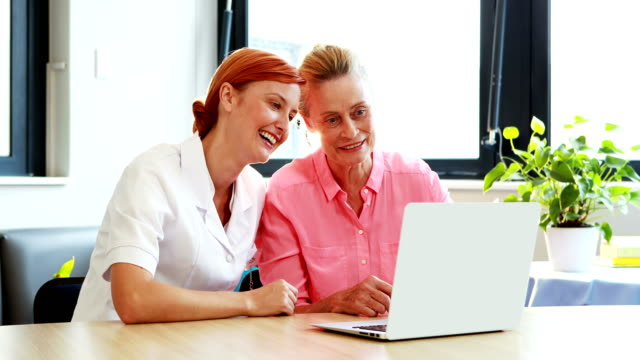 Portrait of nurse and a senior patient using laptop video