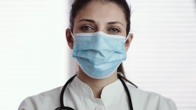 porträtt av sjuksköterska bär ansiktsmask på arbetsplatsen. 4k lager video - face mask bildbanksvideor och videomaterial från bakom kulisserna