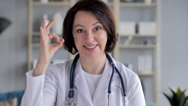 portrait of old lady doctor gesturing  okay sign - znak ok filmów i materiałów b-roll