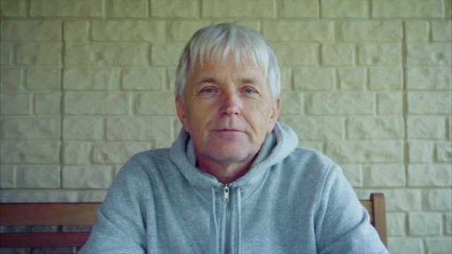 Portrait of old senior man gray hair outside the house sitting on the bench video
