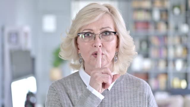 vídeos y material grabado en eventos de stock de retrato de la anciana poniendo el dedo en los labios - dedo sobre labios
