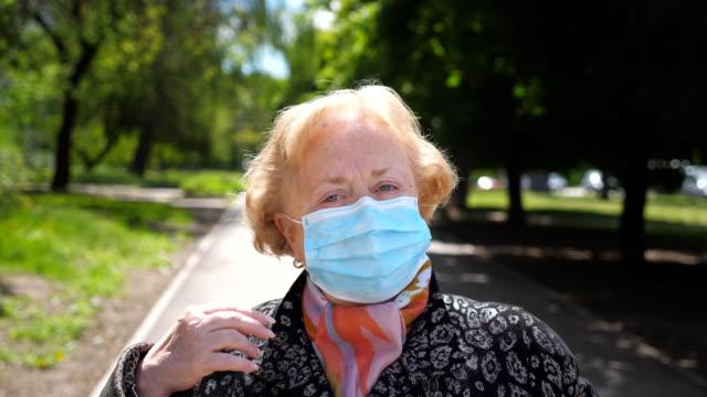 портрет старухи в медицинской маске стоит на улице. бабушка снять защитную маску от вируса covid-19 и серьезные смотрит в камеру. концепция здо� - удалять стоковые видео и кадры b-roll
