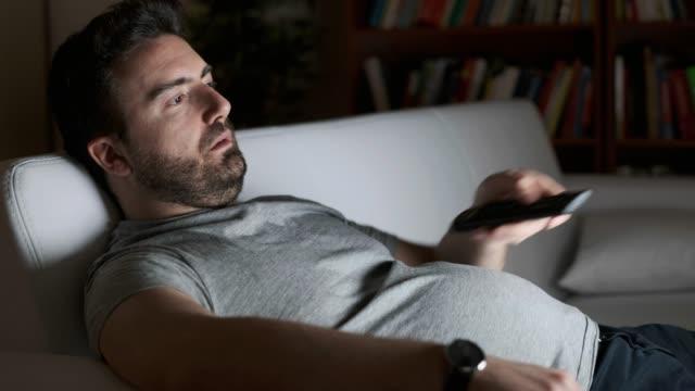 portrait of one caucasian man watching tv - samotność filmów i materiałów b-roll