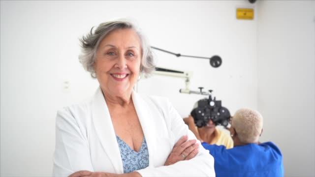 porträt der opthamologist senior ärztin in der klinik - augenheilkunde stock-videos und b-roll-filmmaterial
