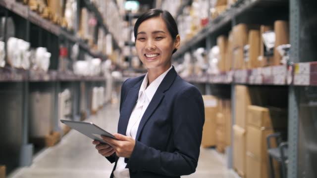 vídeos y material grabado en eventos de stock de retrato de la empresaria asiática propietaria usando tableta digital en su almacén, pequeña empresa - suministros escolares