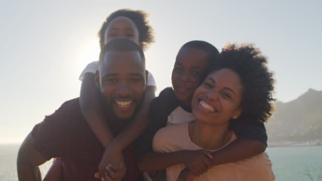 stockvideo's en b-roll-footage met portret van de ouders waardoor kinderen piggybacks by the sea - afrikaanse etniciteit