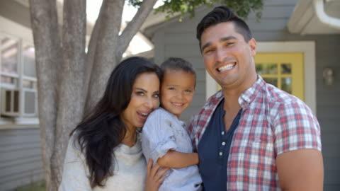 ritratto di genitori in piedi fuori casa abbracciando il figlio - etnia latino americana video stock e b–roll