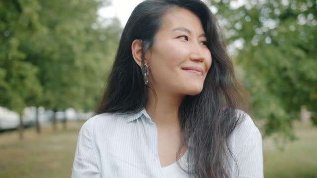 ritratto di donna asiatica perfetta che flirta nel parco sorridendo guardando la macchina fotografica da sola - flirtare video stock e b–roll