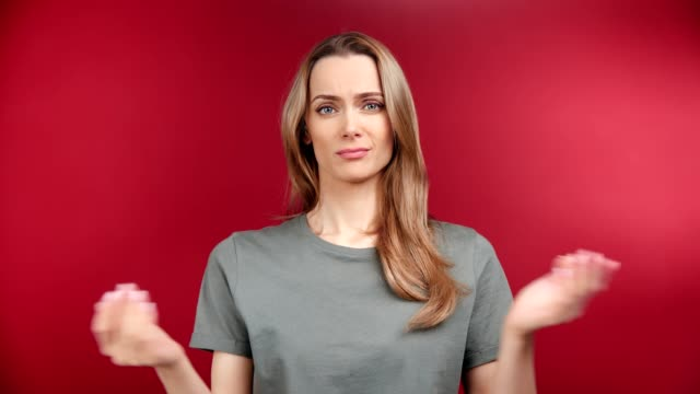portrait of perplexity young woman feeling misunderstanding emotion posing at red studio background - communication problems stock videos & royalty-free footage