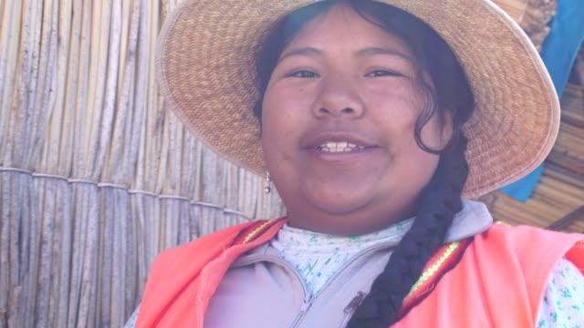 portrait of peruvian woman in uros floating island, lake titicaca, peru - costume tradizionale video stock e b–roll