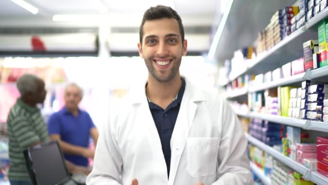 Portrait of pharmacist in a drugstore, customers in the background video